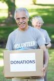 Happy volunteer senior holding donation box Royalty Free Stock Photos