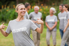 Happy volunteer showing her t-shirt to camera Stock Photo