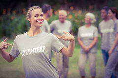 Happy volunteer showing her t-shirt to camera Stock Images