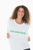 Happy volunteer showing her tshirt to camera Stock Photography
