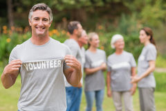 Happy volunteer showing his t-shirt to camera Royalty Free Stock Images