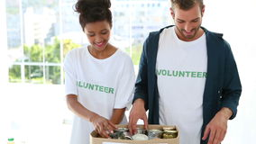 Happy volunteer team packing a food donation box. And smiling at camera stock video footage