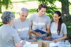 Happy volunteer writing on clipboard Royalty Free Stock Photos