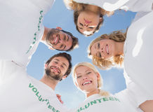 Happy volunteers forming a huddle against blue sky Royalty Free Stock Images