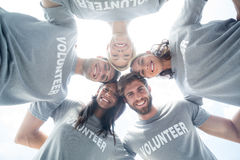 Happy volunteers forming huddle Stock Photo