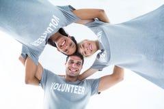 Happy volunteers forming huddle Stock Photo