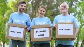 Happy volunteers holding donation cardboxes, humanitarian aid assistance project. Stock footage stock video footage