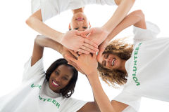 Happy volunteers putting hands together and looking down at camera. On white background Royalty Free Stock Photography