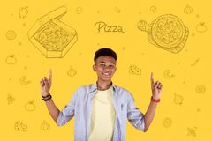 Happy waiter advertising food delivery and pointing to a pizza. Tasty pizza. Cheerful professional waiter suggesting using food delivery and smiling while royalty free stock photo