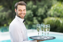Happy waiter carrying champagne flutes on tray. Portrait of happy waiter carrying champagne flutes on tray at poolside Stock Photos
