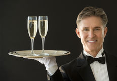 Happy Waiter Carrying Serving Tray With Champagne Flutes. Portrait of happy mature waiter in tuxedo carrying serving tray with champagne flutes isolated on black stock photos