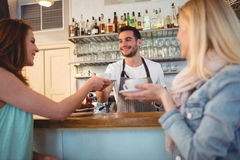 Happy waiter serving coffee to customer at cafeteria. Happy young waiter serving coffee to female customer at cafeteria Stock Images