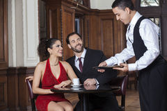 Happy Waiter Serving Coffee To Tango Couple In Restaurant Royalty Free Stock Photos
