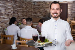 Happy waiter taking care of adults at cafe table. Happy waiter taking care of adults guest at cafe table Stock Images