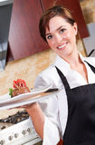 Happy waitress. A young pretty happy waitress holding a plate of dessert with apron on Stock Photos