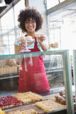 Happy waitress in red apron offering cupcake Stock Photography