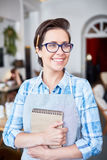 Happy waitress. Successful waitress with notepad waiting for new clients royalty free stock images