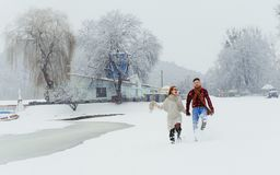 Happy walk of the beautiful loving couple holding hands. Winter fairytale. Meadow location. Happy walk of the beautiful loving couple holding hands. Winter Stock Photos