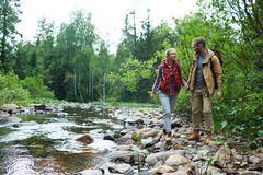 Happy walk. Happy hikers walking along river in the forest Royalty Free Stock Photography