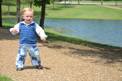 Happy Walking Toddler. Happy baby toddler walking alone in a park on a sidewalk with a pond in view Royalty Free Stock Images