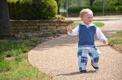 Happy Walking Toddler. Happy baby toddler walking alone in a park on a sidewalk Stock Photography
