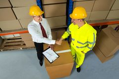 Happy Warehouse Manager And Worker Shaking Hands. Smiling Warehouse Manager And Worker Shaking Hands In Warehouse Royalty Free Stock Photo