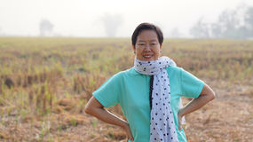 Happy wealthy Asian senior woman wearing scraf in front of her f Royalty Free Stock Images