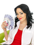 Happy Wealthy Attractive Young Hispanic Woman Holding Money. Happy attractive wealthy Young Woman with long black curly hair and hispanic or european features Royalty Free Stock Photos