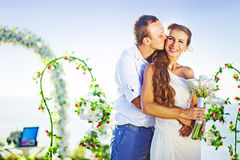 Happy wedding couple. Groom kissing his bride on wedding day near floral arch on wedding venue Royalty Free Stock Photo