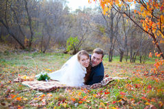 Happy wedding couple in autumn winter forest, lying on plaid hug Royalty Free Stock Photos