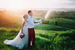Happy wedding couple with buttle of champaine and splashes of champagne Stock Photo