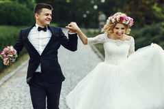 Happy wedding couple charming groom and blonde bride dancing in Stock Photos