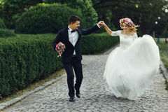 Happy wedding couple charming groom and blonde bride dancing in Stock Image