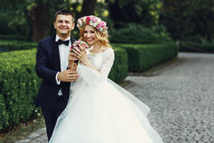 Happy wedding couple charming groom and blonde bride laughing in. Park Stock Photography
