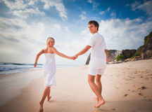 Happy wedding couple dressed in white running at beach Stock Image