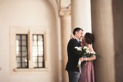 Happy wedding couple, groom, bride with pink dress hugging and smiling each other on the background walls in castle Stock Photography