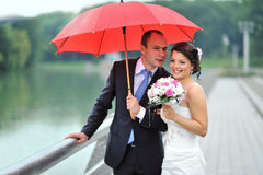 Happy wedding couple hiding from rain Royalty Free Stock Photography