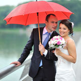 Happy wedding couple hiding from rain - portrait Stock Images