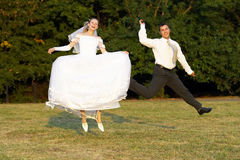 Happy wedding couple � jump Stock Photo