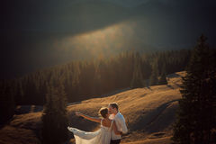 Happy wedding couple kiss on sunset in the mountains. Honeymoon. Happy wedding couple kiss on sunset in the mountains. Honeymoon Royalty Free Stock Images