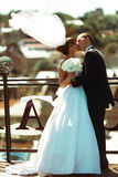 Happy wedding couple kisses on the roof in a windy weather.  Royalty Free Stock Image