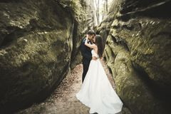 Happy wedding couple kissing and hugging near a high cliff Stock Photo