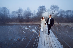 Happy wedding couple laughing and having fun on the suspension bridge in mountains Royalty Free Stock Photography
