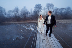 Happy wedding couple laughing and having fun on the suspension bridge in mountains Royalty Free Stock Photo