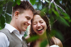 Happy wedding couple laughing in the park royalty free stock images