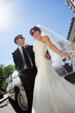 Happy Wedding Couple with Limo Royalty Free Stock Photo