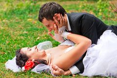Happy wedding couple lying on the grass Royalty Free Stock Photos