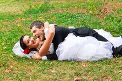 Happy wedding couple lying on the grass Stock Image