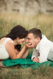 Happy wedding couple lying on green grass at the summer time Stock Photo