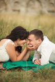 Happy wedding couple lying on green grass at the summer time Royalty Free Stock Images